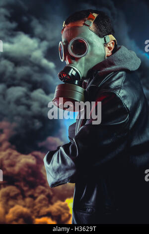 Armed man with gas mask over explosion background - Stock Photo