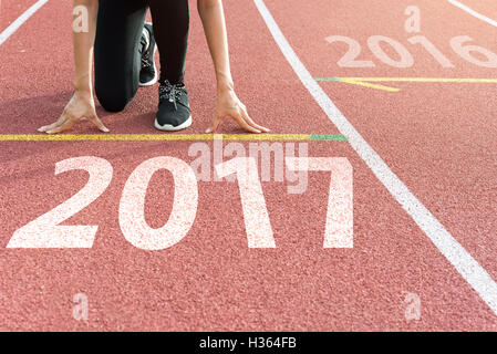 Athlete on starting line waiting for the start in running track with text 2017 year, Start to new year 2017 - Stock Photo