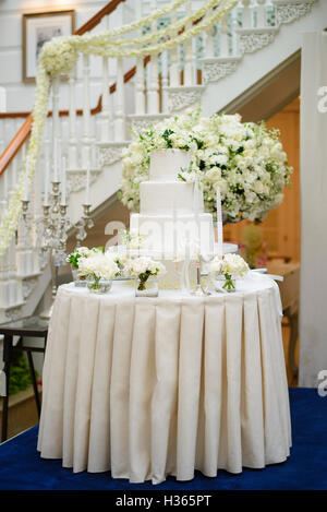 Wedding cake surrounded by white flowers - Stock Photo