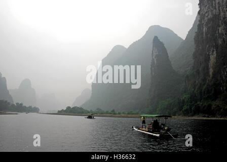 Passengers enjoy a bamboo raft ride along the idyllic Li River on a misty day in Guangxi, China. - Stock Photo