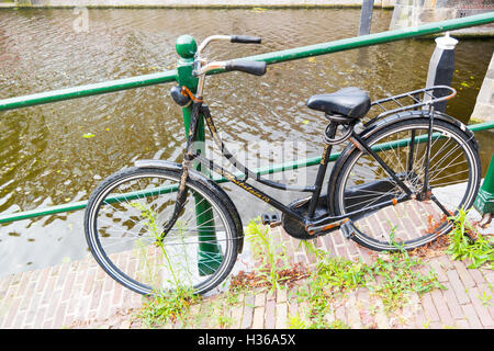 Old bicycle parked by railing on quayside of canal - weed and cigarette butts on the street in downtown Leiden, - Stock Photo