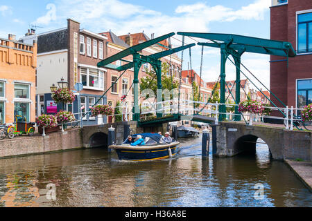 People cruising in barge under drawbridge over Old Rhine canal in old town of Leiden, South Holland, Netherlands - Stock Photo