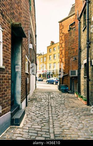 A narrow cobbled street in Highgate Village, London, UK - Stock Photo