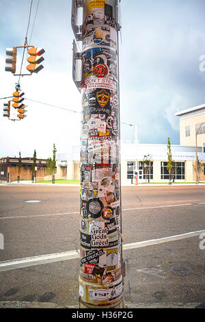 Light pole on sidewalk with 100 graffiti stickers promoting bands, music, concerts, located in front of Sun Studio, - Stock Photo