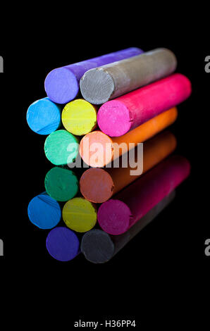 Flower-shaped colored chalk in variety of colors on a black background - Stock Photo
