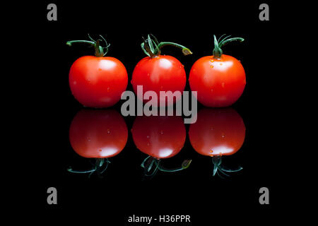 Three tomatoes on a black shiny background - Stock Photo