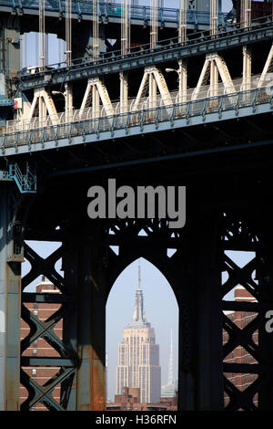 The view of Empire State Building through the arch of the steel tower of Manhattan Bridge in Brooklyn.New York City.USA - Stock Photo