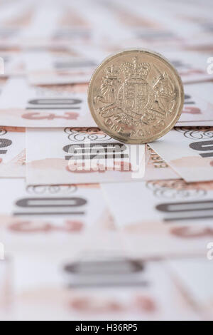 Fanned out £10 banknotes with £1 coin - as visual metaphor for concept of UK currency, wages, economy and inflation. - Stock Photo