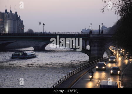 The twilight view of riverside traffics and Pont au Change over River Seine in background. Paris.France - Stock Photo