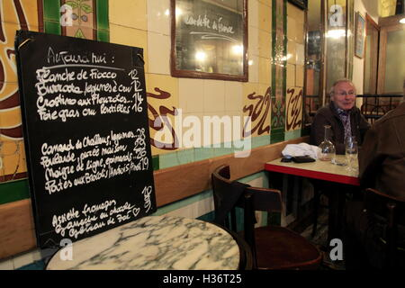 Hand writing menu's on a blackboard displaying in a small restaurant in Paris.France - Stock Photo