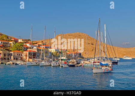 Private sailing yacht  arriving at small marina and pontoons in Chalki, Island of Chalki, Dodecanese Islands,Greece. - Stock Photo