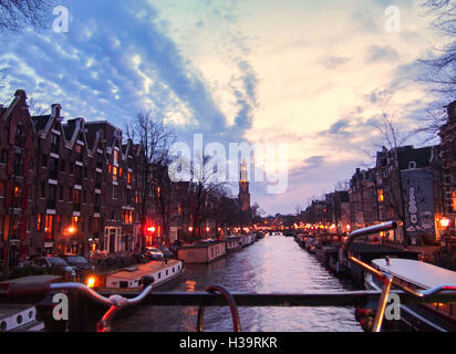 View of a canal from the bridge in Amsterdam at twilight during winter - Stock Photo