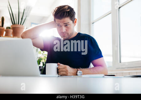 Young man holding coffee cup and looking at laptop while sitting at his desk in office. Thoughtful business man - Stock Photo