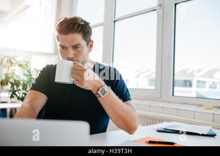 Young businessman drinking coffee and working on laptop at office. Male executive working at his desk and drinking - Stock Photo