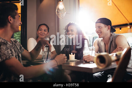 Group of friends sitting in cafe and having fun. Teenagers relaxing on coffee shop. - Stock Photo