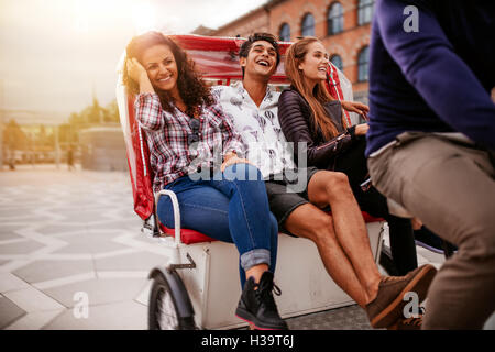 Teenage friends enjoying tricycle ride in the city. Teenagers riding on tricycle on road and smiling. - Stock Photo