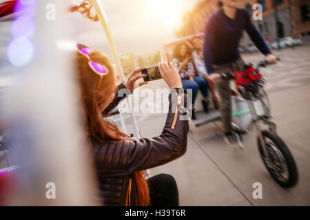 Woman photographing friends riding tricycle on road. Young people on tricycle on city street. - Stock Photo