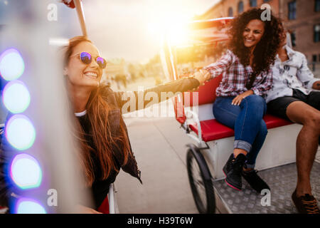 Best friends enjoying tricycle ride in the city. Teenage girls riding on tricycles and holding hands. - Stock Photo