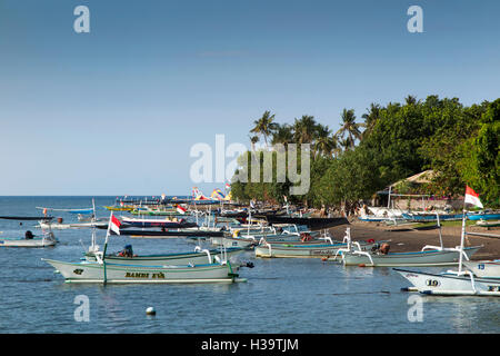 Indonesia, Bali, Lovina, fishing boats on main beach and moored in sea - Stock Photo