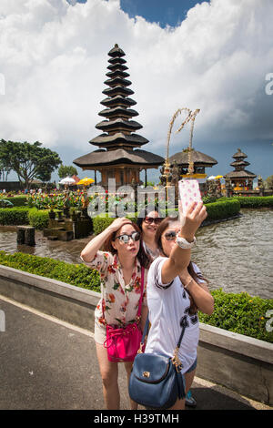 Indonesia, Bali, Candikuning, Pura Ulun Danu Bratan temple, Chinese tourists taking selfies at pagoda on lake - Stock Photo