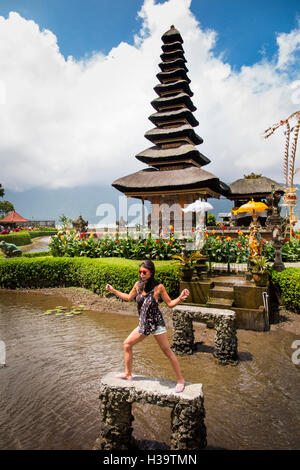 Indonesia, Bali, Candikuning Pura Ulun Danu Bratan temple, tourist posing for picture at pagoda on lake - Stock Photo