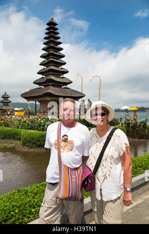 Indonesia, Bali, Candikuning, Pura Ulun Danu Bratan temple, older tourists posing for picture at pagoda on lake - Stock Photo