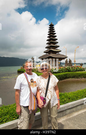 Indonesia, Bali, Candikuning, Pura Ulun Danu Bratan temple, senior tourists posing for picture at pagoda on lake - Stock Photo
