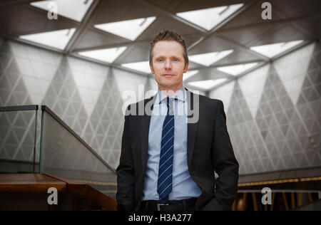 Confident businessman standing in a corporate building. - Stock Photo