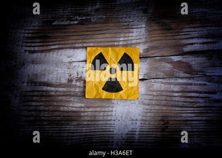 Radiation warning sign on a wooden surface. Close up. - Stock Photo