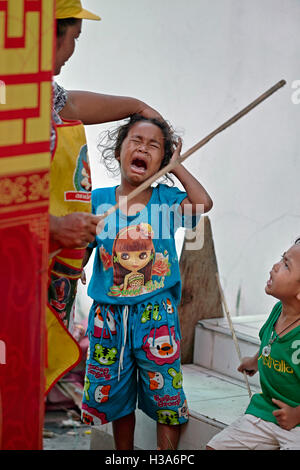 Mother scolding her crying daughter and wielding a stick. Thailand S. E. Asia - Stock Photo