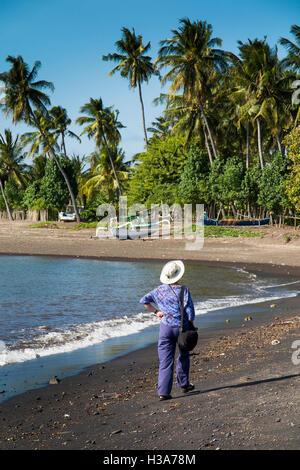 Indonesia, Lombok, Selengan, fishing village, tourist walking on black volcanic sand beach - Stock Photo