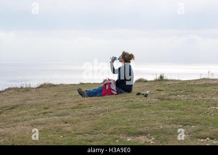 Taking a water break. Walking the south west coastal path of England involves lots of downs and ups. Thirsty work. - Stock Photo