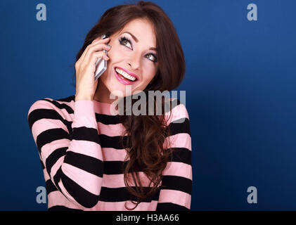Beautiful makeup excited woman talking on mobile phone and with thoughtful look looking up on bright blue background. - Stock Photo
