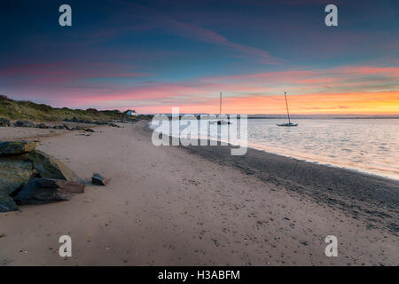 Stunning sunrise over a white cottage on the beach at Crow Point at Braunton near Barnstaple in Devon - Stock Photo