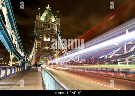 Long exposure of light streaks caused by a double decker bus at night on the famous London Bridge in London. - Stock Photo