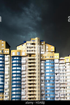 Apartment building under the heavy black rainy clouds - Stock Photo