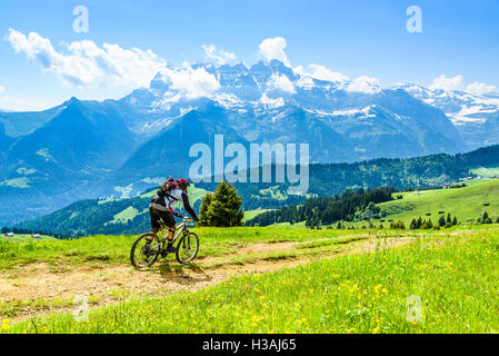 Rider participating in Pass'Portes du Soleil MTB 2016, with view of the Dents du Midi - Stock Photo