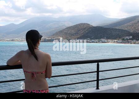 A lady looks out onto Stalis Stalida Crete Greece - Stock Photo