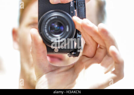 Young man is taking a photograph with a small compact digital camera - Stock Photo