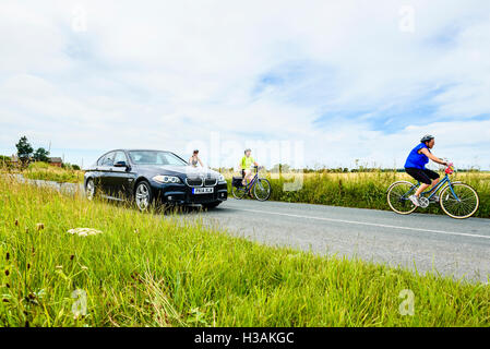 Car passing group of female cyclists on road near Hesketh Bank in West Lancashire England UK - Stock Photo