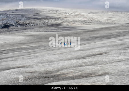 People with dogsleds and dogs on a glacier in Iceland. - Stock Photo