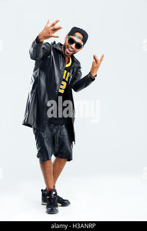 Portrait of a happy afro american man in stylish cloth posing over black background - Stock Photo