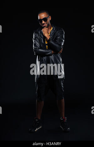 Stylish afro american man looking at camera and posing over black background - Stock Photo