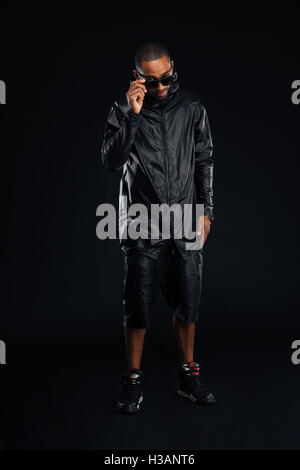 Smiling stylish afro american young man in sunglasses posing over black background - Stock Photo