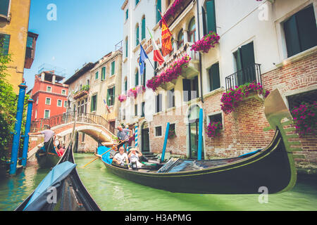 Traditional gondolas on canal in Venice, Italy with retro vintage Instagram tone filter effect on a sunny day in - Stock Photo