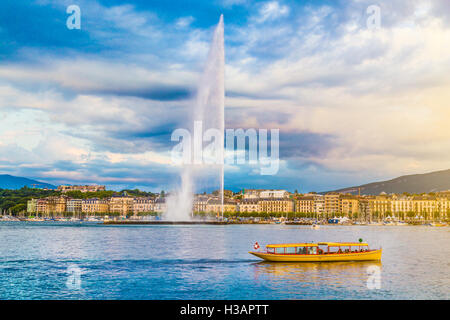 Classic view of Geneva skyline with famous Jet d'Eau fountain at Lake Geneva in beautiful evening light at sunset, - Stock Photo