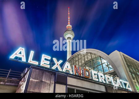 Classic wide-angle view of Alexanderplatz neon sign with famous TV tower and train station at night Berlin, Germany - Stock Photo