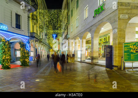 LUGANO, SWITZERLAND - DECEMBER 29, 2015: Evening scene in Via Nassa Street, with Christmas decorations, locals and - Stock Photo