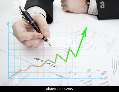 businessman holding a pen and counts the budget and diagram - Stock Photo