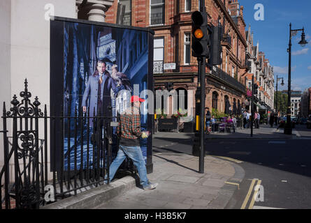 A workman steps on to street level in front of a construction hoarding featuring a male with a bird of prey on his - Stock Photo